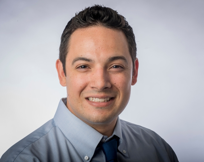 Headshot of Cruz Medina wearing a gray shirt and blue tie